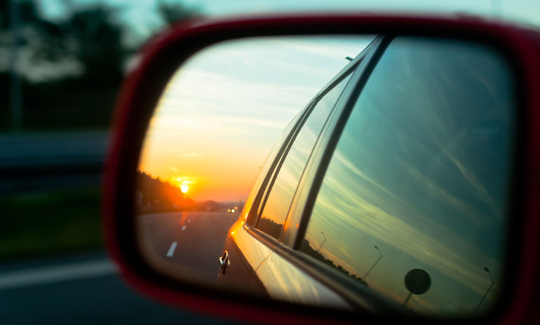 close up of a car rearview mirror showing the road behind