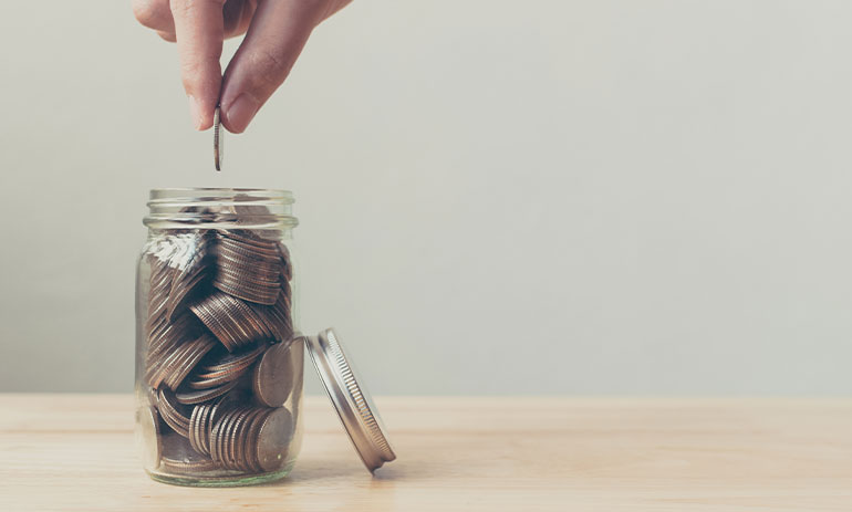 person putting a coin in a jar