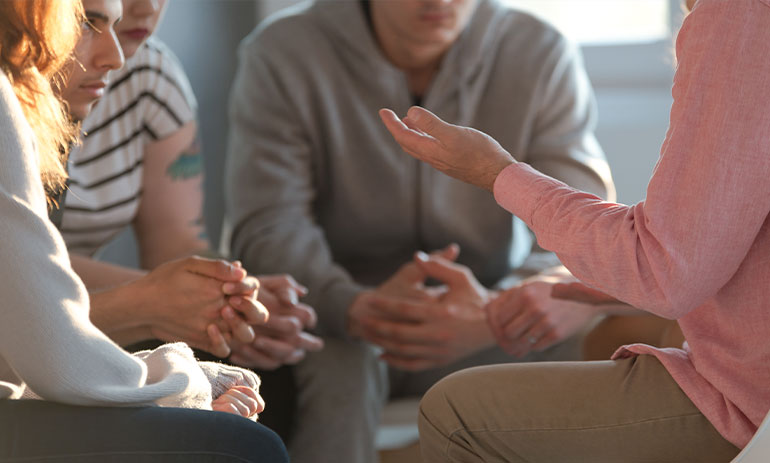 close up of group of people sitting in a circle talking at a support group