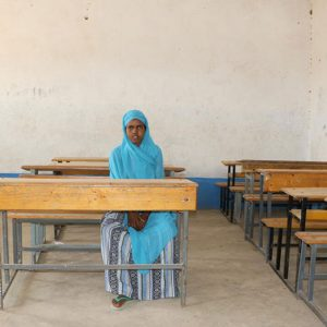 Young girl, Aisha, sitting alone in a classroom in Ethiopia.