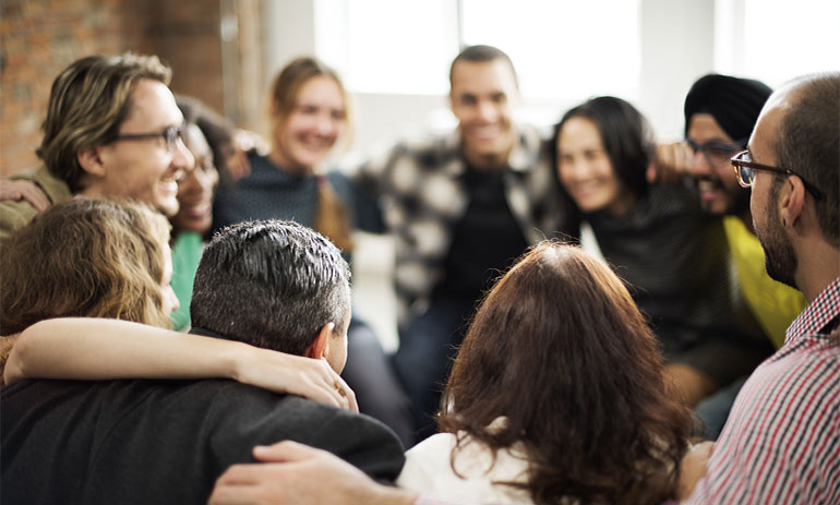 group of people in a circle with their arms around each other