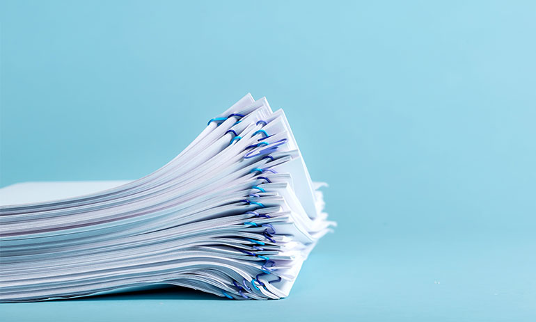 stack of paperwork on a blue background