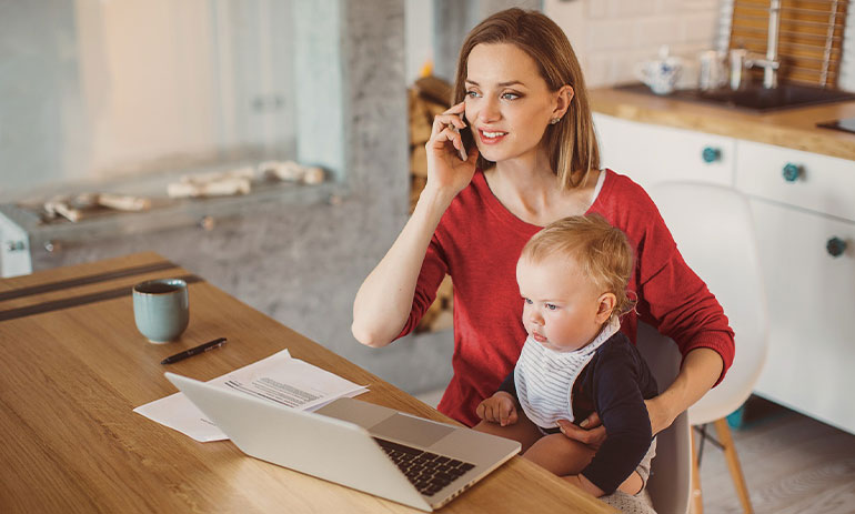 Woman sitting at the table in her kitchen with her laptop, speaking on her mobile while holding a baby on her knee