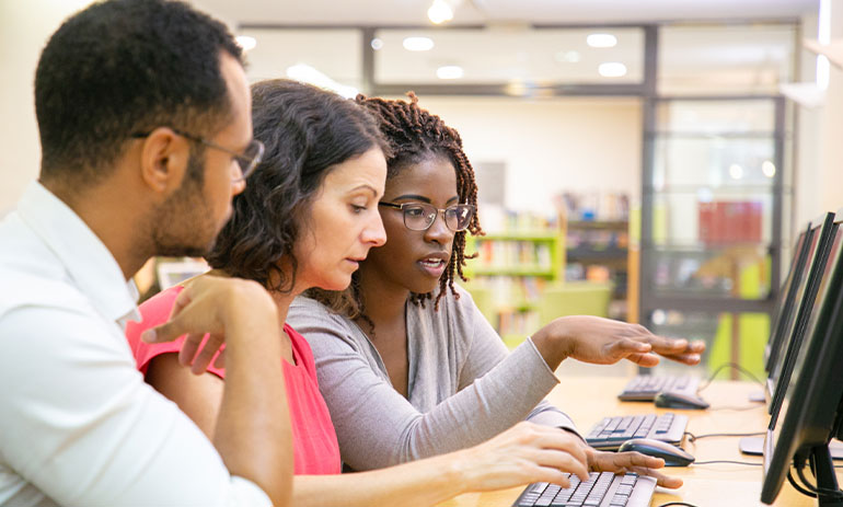 three young people on computer