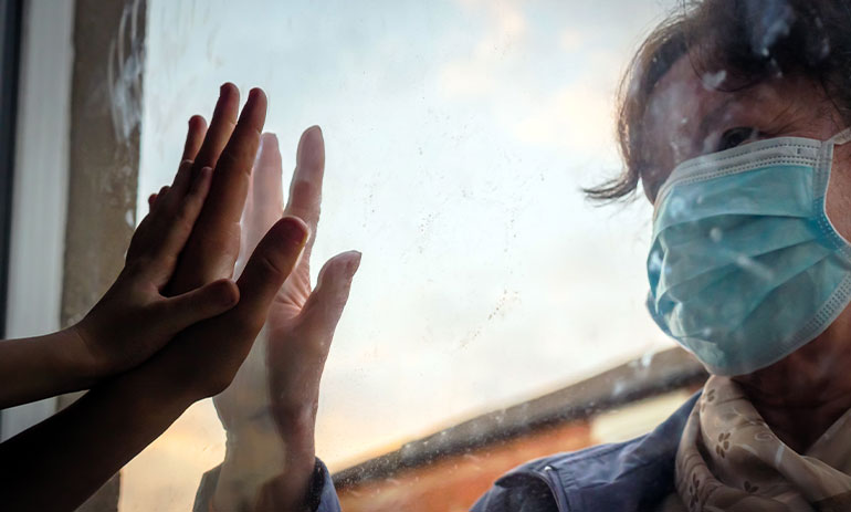 a woman wearing a facemask touching her hand to a window, with hand touching the other side