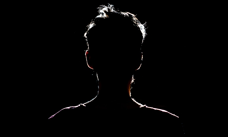 silhouette of man in dark place