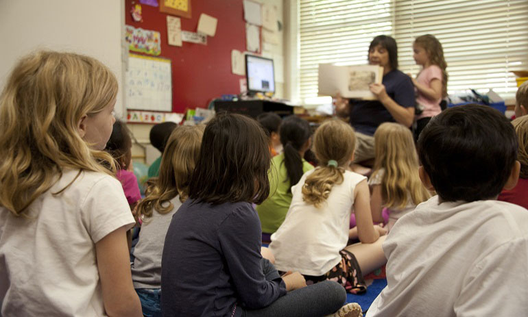 children sitting in a classroom listening to the teacher read a book