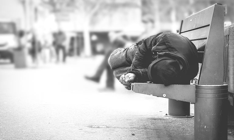 black and white image of man sleeping on a park bench