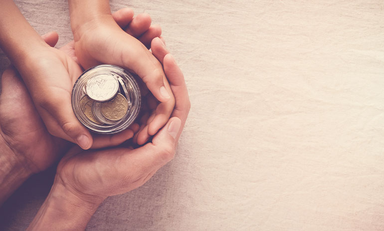 hands holding a jar of coins