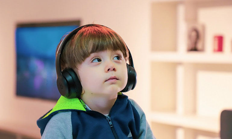 Young child with disability wearing headphones