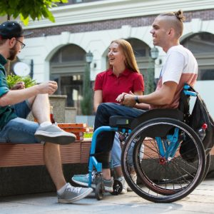 Person in wheelchair conversing with friends in public