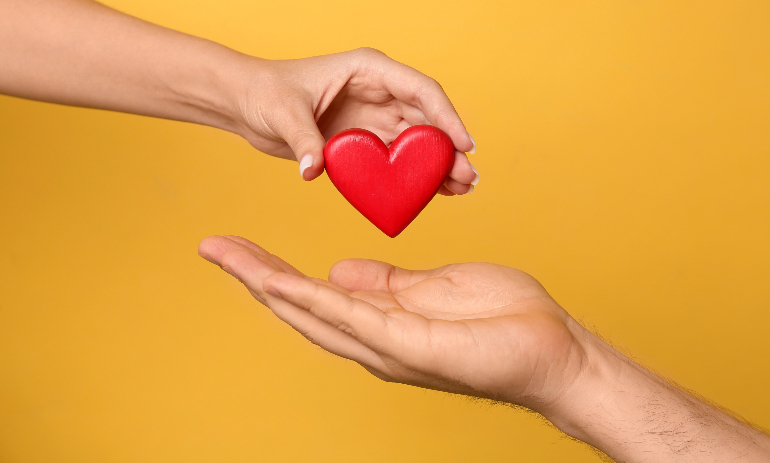 Woman giving red heart to man on yellow background